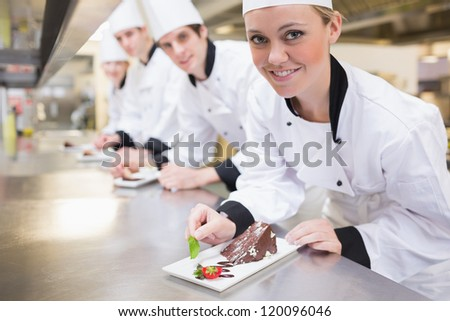 Smiling Chef's finishing dessert plates in the kitchen - stock photo