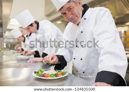 Smiling Chef's preparing their salads in the kitchen
