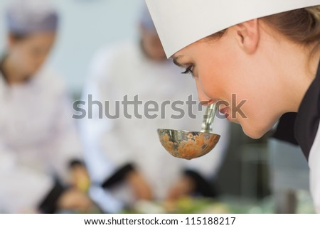 Smiling chef smelling the soup in kitchen