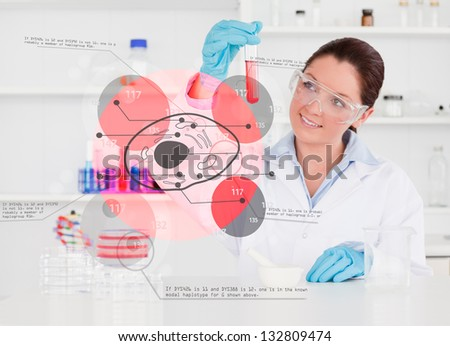 Smiling chemist looking at test tube of red chemical with holographic cell interface