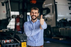 Smiling chief standing in auto park and showing thumbs up. In background are trucks. Firm from import and export.