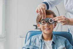 Smiling child boy in glasses checks eye vision at pediatric ophthalmologist