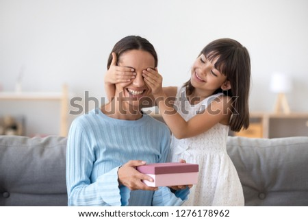 Smiling child daughter closing eyes of excited mom holding pink gift box congratulating mum celebrating birthday with mommy at home together, cute kid girl making surprise present on mothers day
