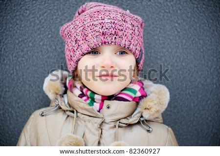 Smiling child girl wearing pink knitted hat and striped scarf - stock photo