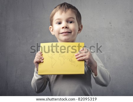 Smiling child holding a paper sheet with the Earth on it