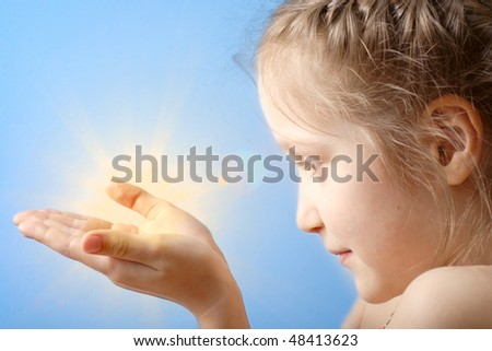 smiling child holding a sun at her hands on a blue sky background