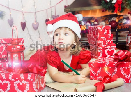 Smiling child in a cap of Santa Claus with holiday wish list