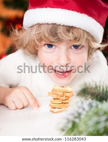 Smiling child in Santa`s hat eating Christmas cookies