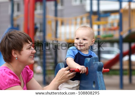Smiling child is playing on wooden horse at playground