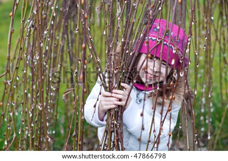 Smiling child looking from behind willow branches - stock photo
