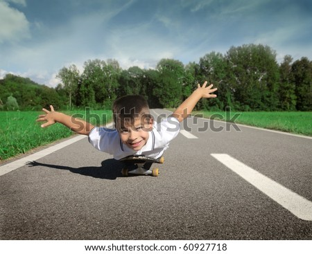 Smiling child lying on a skateboard on a countryside road - stock photo