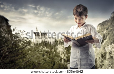 Smiling child reading a book with fairy tale castle in the background