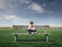 Smiling child sitting on a park bench with green meadow on the background