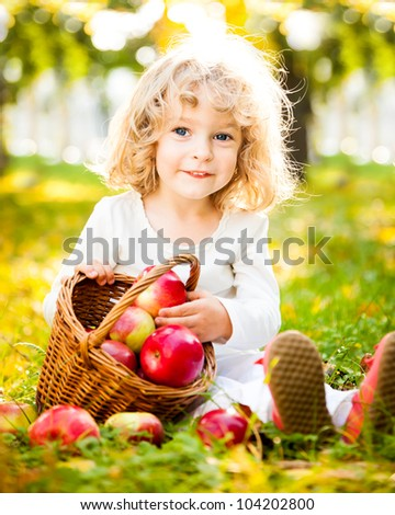 Smiling child with basket of red apples sitting on yellow leaves in autumn park