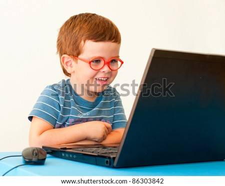 Smiling child with glasses using computer