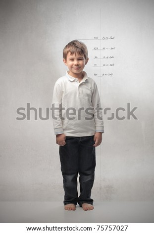 Smiling child with measures of growth beside him