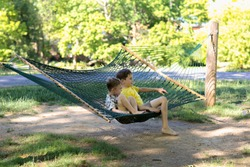 smiling children are sitting in a hammock. relaxed kids in a hammock. blurred background. copy space for your text