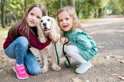 Smiling children girls hugging  their dog outdoor. Portrait of siblings with puppy on walk in warm autumn day. Pets and kids companionship concept. Selective focus