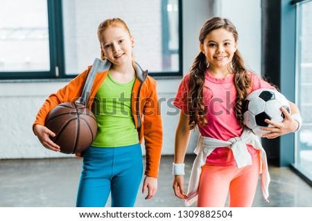 Smiling children in sportswear holding balls in gym