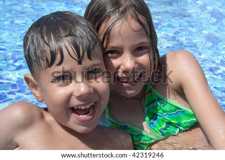 Smiling children in the swimming pool of water park in sunny summer day