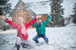 smiling children playing on snow in winter holiday