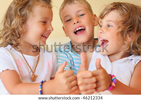 Smiling children three together in cozy room shows ?? gesture