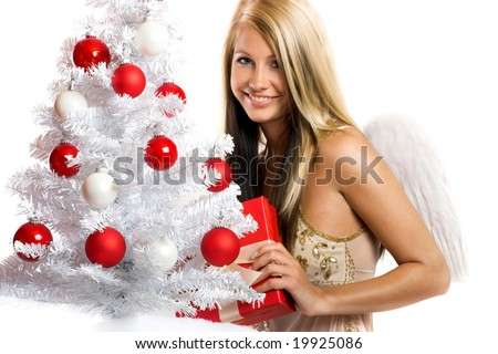 smiling christmas angel isolated on white background with a christmas-tree and a gift