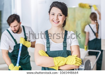 Smiling cleaning lady in a green uniform and yellow rubber gloves at work #1065448664