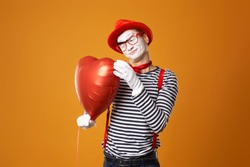 Smiling clown mime in red hat and vest holds heart ball in his hands on orange background