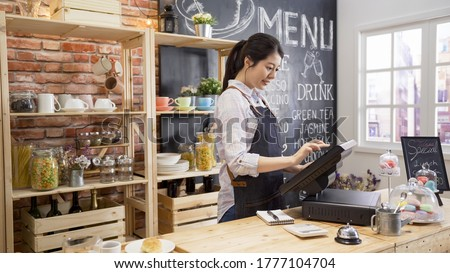 smiling coffee shop assistant using pos point of sale terminal to put in order from note paper at restaurant register. waitress lady working in counter in cafe store. young girl staff using cashbox.