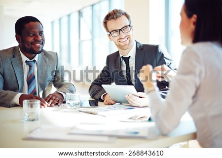 Smiling colleagues discussing working ideas in office #268843610