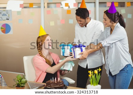 Smiling colleagues giving birthday gifts to businesswoman in office