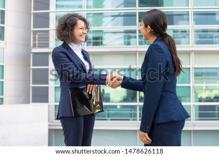 Smiling colleagues standing on street and shaking hands. Cheerful young confident employees wearing formal suits transferring documents. Business confidence concept