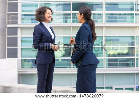 Smiling colleagues standing on street and talking. Cheerful young confident employees wearing formal suits looking at each other. Business confidence concept