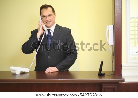 Smiling concierge behind the counter at his workplace answers to phone calls in a luxury apartment building