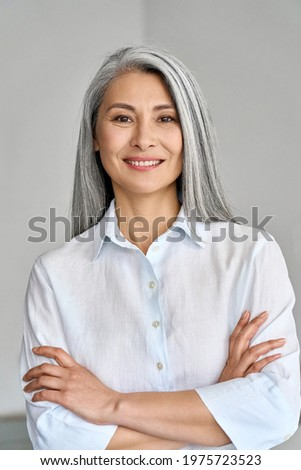 Smiling confident adult 50 years old Asian female professional standing arms crossed looking at camera at gray background. Portrait of sophisticated grey hair woman advertising products and services.