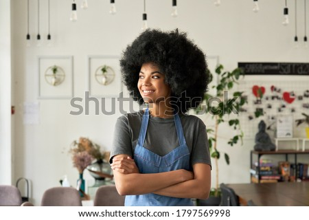 Smiling confident African American young woman with Afro hair modern cafe small business owner, female waitress in restaurant looking away standing arms crossed in cozy coffee shop interior. Portrait.
