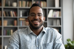 Smiling confident african male applicant online teacher look at webcam video calling chatting for distant job interview, ethnic hipster man blogger record vlog on camera, headshot closeup portrait