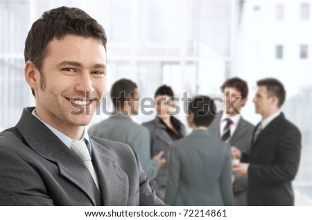 Smiling confident businessman portrait, group of businesspeople chatting in background.?