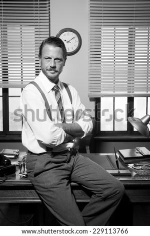 Smiling confident businessman sitting on vintage office desk.
