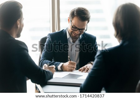 Smiling confident businessman wearing glasses signing contract at group negotiations, business partners making successful investment deal, agreement, salesman putting signature on legal documents
