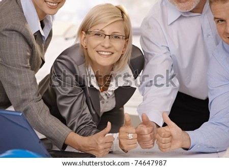 Smiling confident businesswoman giving thumbs up with team in office.?