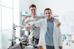 Smiling confident engineering students posing in the lab and leaning on a 3D printer, education and innovation concept
