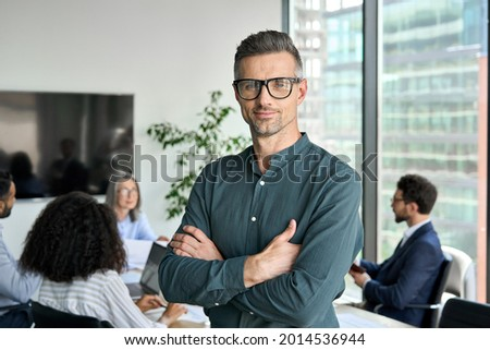 Smiling confident mature businessman leader looking at camera standing in office at team meeting. Male corporate leader ceo executive manager wearing glasses posing for business portrait arms folded.