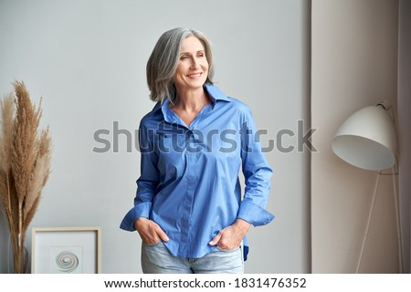 Smiling confident mature woman standing indoors looking at window. Stylish elegant middle aged senior 60s gray-haired lady thinking of good future vision, enjoying wellbeing, dreaming at home.