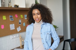 Smiling confident pretty millennial africanamerican woman look at camera standing at home office. Happy mixed race afro ethnic female college student, remote worker, professional freelancer portrait.