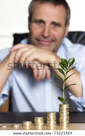 Smiling confident senior business person sitting at desk in front of increasing stacks of coins with growing green plant, looking forward to developing business growth.