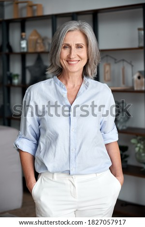 Smiling confident stylish mature middle aged woman stand at home office. Old senior elegant businesswoman, 60s gray-haired lady executive business leader manager looking at camera, vertical portrait.