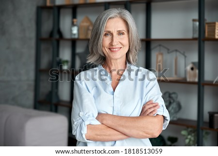 Smiling confident stylish mature middle aged woman standing at home office. Old senior businesswoman, 60s gray-haired lady executive business leader manager looking at camera arms crossed, portrait.