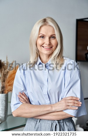 Smiling confident stylish 50s middle aged woman standing at home office. Older businesswoman, lady executive business leader, manager or entrepreneur looking at camera arms crossed, portrait.